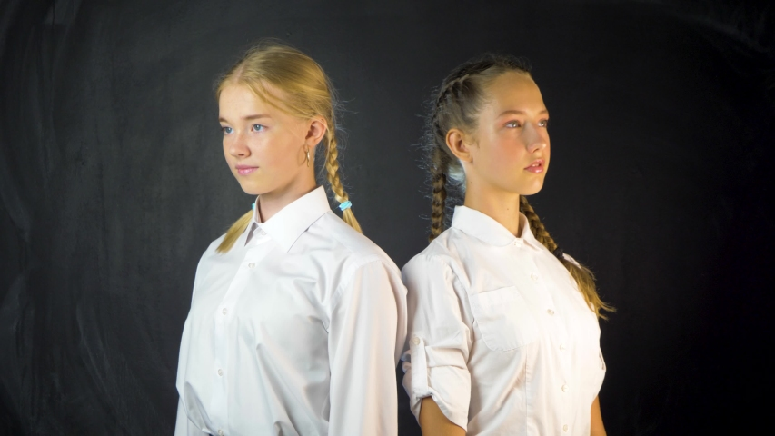 Two young school girls in class on the background of blackboard. Cute schoolgirls in uniform smiling and look at the camera. | Shutterstock HD Video #1057407832