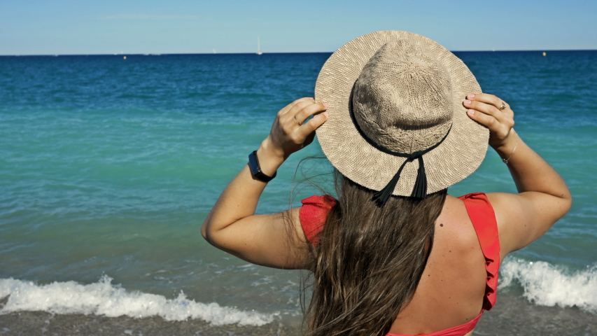 Young woman in a wide-brimmed hat stands by the sea and looks into the distance. Against the background of the blue sky and the sea. Back view. | Shutterstock HD Video #1057407988