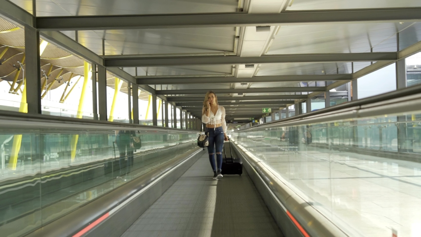 Woman walking with her suitcase through the airport | Shutterstock HD Video #1057408066