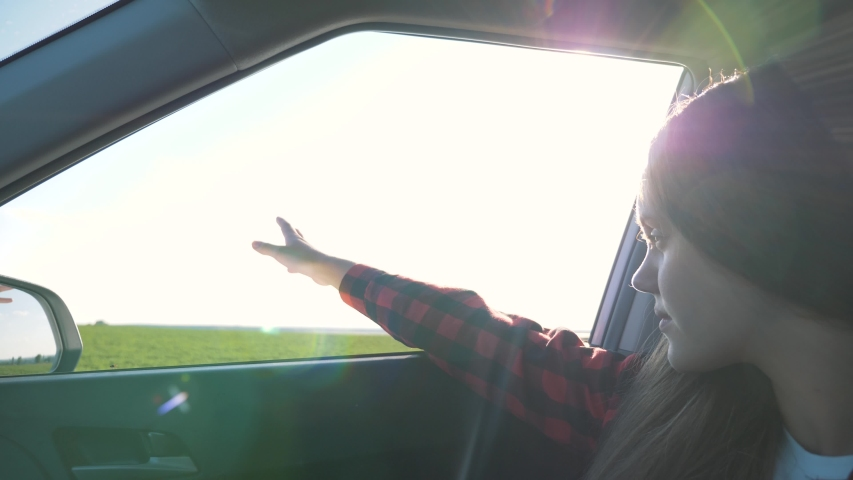 The girl is traveling by car. The child is sitting in the front seat of the car with his hand out the open window. A teenage girl waves her hand, catching the glare of the sun. | Shutterstock HD Video #1057408108