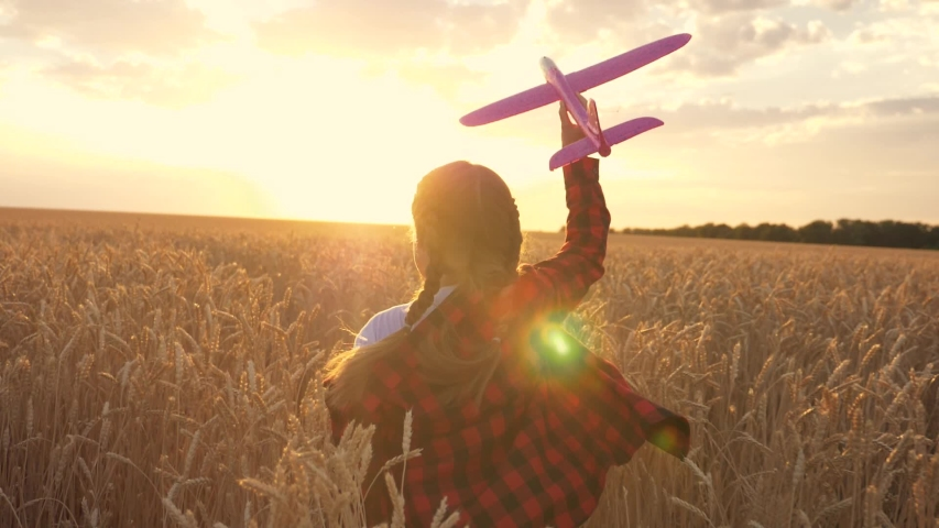 A happy child runs across a field with a toy airplane at sunset. Children play with a toy plane. The girl dreams of flying and becoming a pilot. | Shutterstock HD Video #1057408114