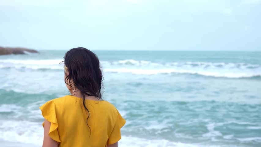 Portrait of beautiful brunette lady in a yellow dress enjoys the wind breeze while walking along the beach by the bay. Posing on camera | Shutterstock HD Video #1057409113