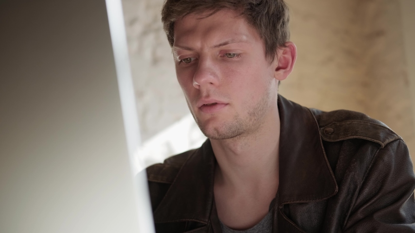 The camera slowly approaches the face of a young man sitting in front of a laptop screen and concentrating on typing a message. The businessman is puzzled, frowns and strains his face. | Shutterstock HD Video #1057409536
