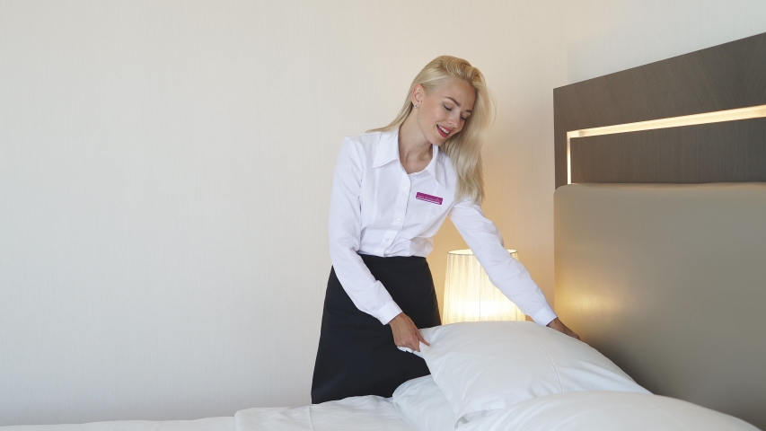 Caucasian blonde female chambermaid making bed in hotel room, hotel service concept | Shutterstock HD Video #1057410391