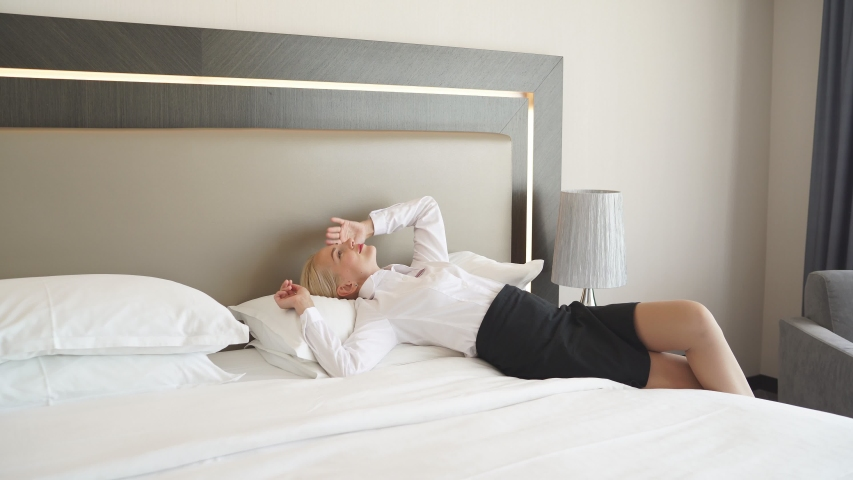 Chambermaid is exhausted after cleaning hotel room, woman lie on bed, tired. hotel service concept | Shutterstock HD Video #1057410397
