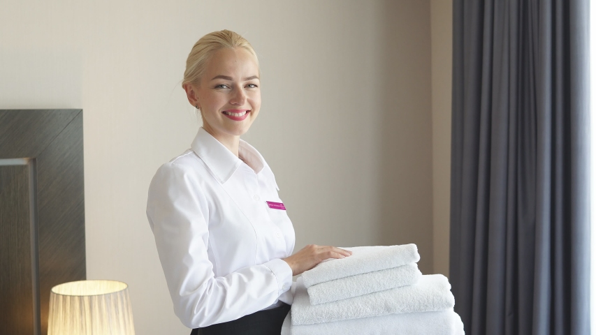 Portrait of attractive chambermaid with towels in hands, charming woman stand in tidy room, prepares a room for guests | Shutterstock HD Video #1057410400