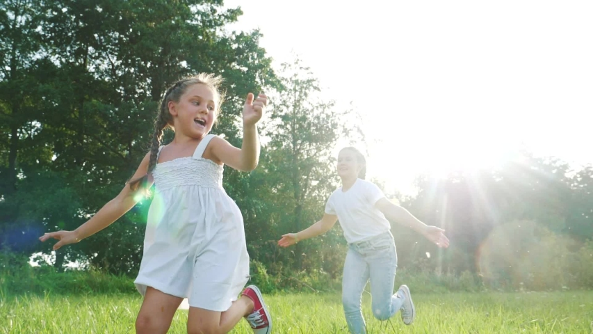 children kid dream together run in the park at sunset. happy family people in the park concept. two sisters playing catch-up run. baby child fun running in green meadow. happy family dream kid concept Royalty-Free Stock Footage #1057410964