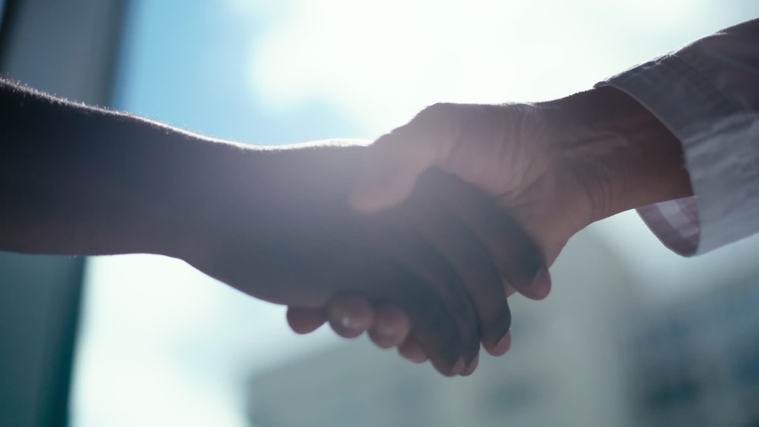 Close-up handshaking of two colleagues African business man and Caucasian businessman background of window, sunlight. Tracking shot in slow motion. Concept of interracial friendship and cooperation.