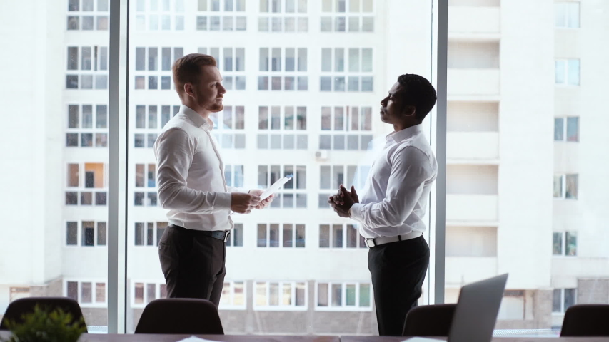 Side view of Caucasian businessman and African American businessman agreed contract and shaking hands in conference room background of window and office building. Concept of interracial cooperation.
