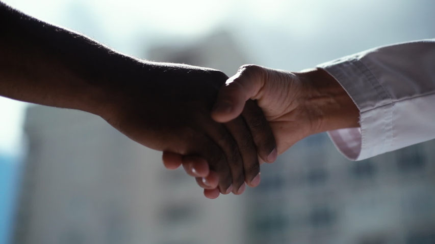 Close-up of handshake African man and white woman on background of window and cityscape. Concept of handshaking black and white hand, interracial friendship and cooperation. Shooting in slow motion.