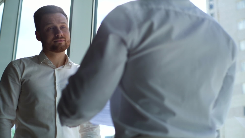 Tracking shot of Caucasian businessman and African American businessman agreed contract and shaking hands in conference room background of window, from below. Concept of interracial cooperation.