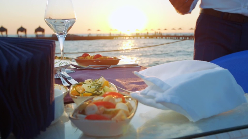 The waiter drops the fish dish to the dining table set up on the pier. sunset. seaside. slow motion.