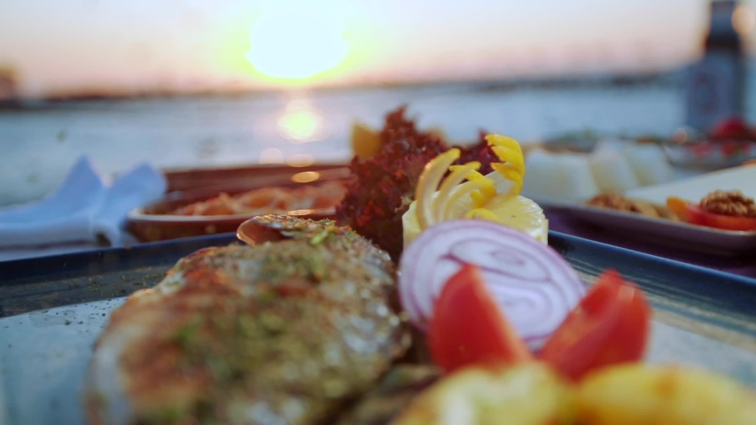 Dining table prepared by the sea at sunset. in slow motion, the waiter throws spices into the fish on the plate. Royalty-Free Stock Footage #1057413421