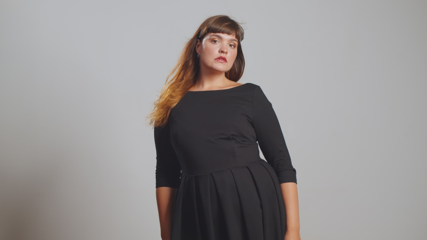 Plus size fashion model in beautiful dress posing at camera isolated. Fat woman on gray studio background. Overweight female and body positive concept