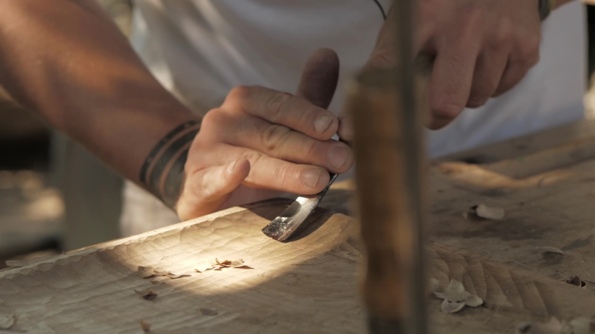 a woodcarver processes a walnut wood board with a chisel. artisan makes a tea tray Royalty-Free Stock Footage #1057424011