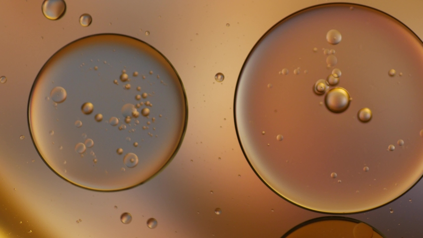 Gold artistic of oil drop floating on the water. Pastel color bubble for background. Orange background of oil drop. Royalty-Free Stock Footage #1057424200