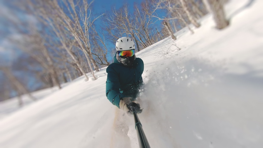 Man riding on snowboard with selfie stick in his hand between trees on slow motion. Guy doing snow splash rising on magnificent sunny day. Concept of extreme, sport, winter, freeride, snowboarding | Shutterstock HD Video #1057431280