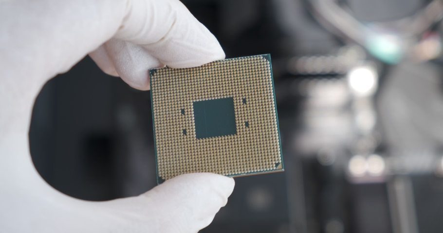 CPU processor comes into focus held by technician with white latex rubber gloves. Custom PC build concept, upgrading computer hardware. Royalty-Free Stock Footage #1057432705