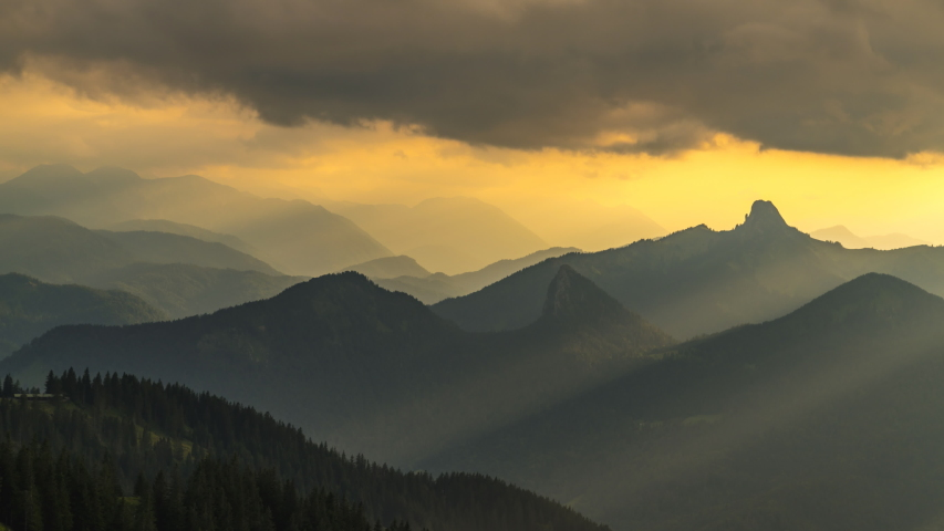 Timelapse of sun rays emerging though the dark storm clouds in the mountains at sunset bavaria germany alps mountains