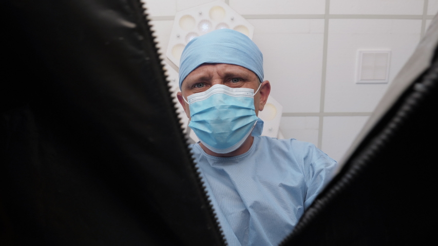 The pathologist opens a plastic bag with a dead body inside the hospital morgue. A corpse in a black plastic bag. First-person view, conceptual footage