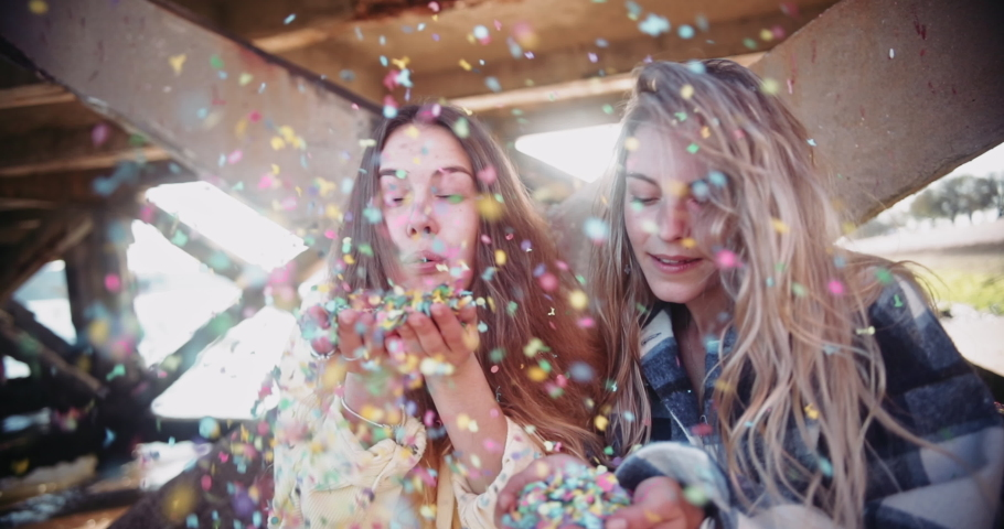 Close up young blonde women blowing colorful confetti by pier | Shutterstock HD Video #1057440634