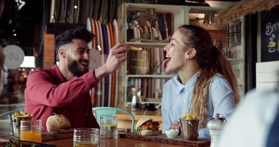 Young middle-eastern man feeding frie to blonde friend at restaurant | Shutterstock HD Video #1057440772