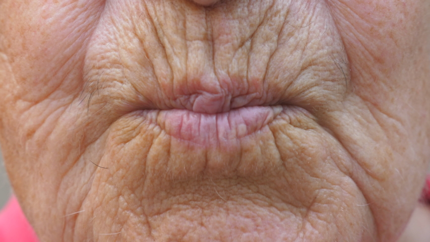 Close up lips of mature grandmother. Mouth of elder grandma sends air kiss into camera. Senior woman with wrinkled skin does kissing gesture. Slow motion | Shutterstock HD Video #1057443907