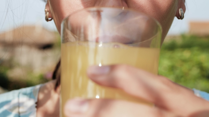 Woman is drinking orange juice. Female hand bring glass with orange juice to their mouth and drink it on sunny day in nature. Close-up