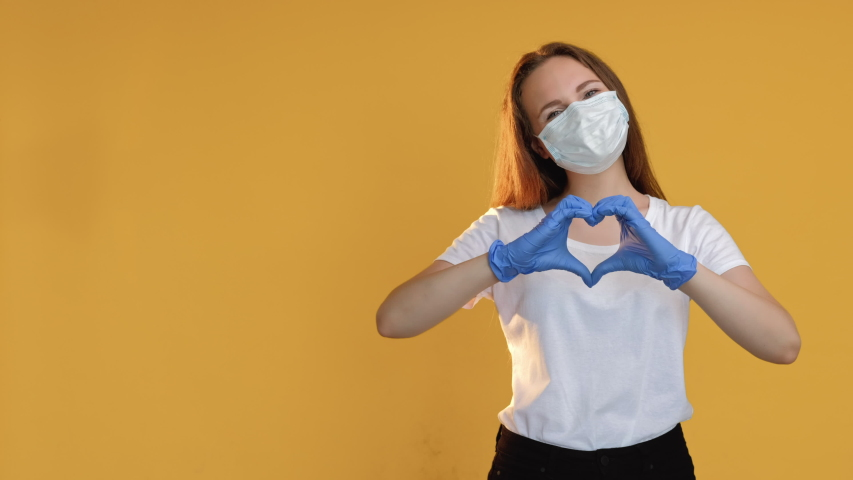 Love signal. Health charity. Optimistic woman in protective face mask gloves blowing air kiss showing heart gesture isolated on beige copy space. Coronavirus pandemic. Devotion message set of 3. Royalty-Free Stock Footage #1057451929