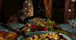 Close up shot of table covered with healthy vegan mediterranean food. People filling up their plates and glasses at dinner party table low angle 4k footage