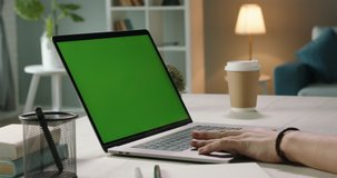 Close up shot of hands of freelancer working with chroma key green screen laptop, using trackpad scrolling through website - technology concept 4k video template