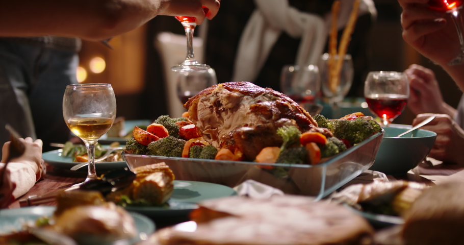 People having a thanksgiving dinner party. Close up shot of table filled with salads and tasty roasted turkey. Family filling up plates with food 4k footage | Shutterstock HD Video #1057452769