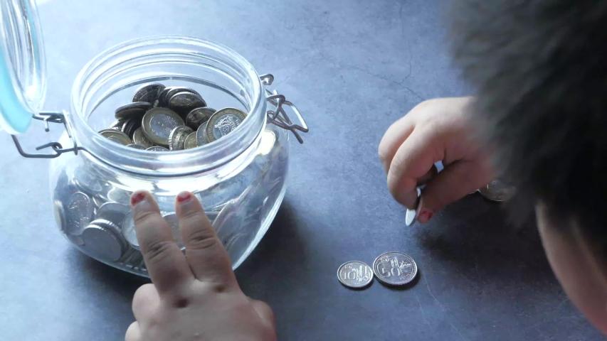 Child girl saving coins in a jar  | Shutterstock HD Video #1057456894
