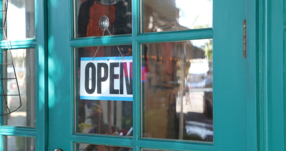 Store owner closing and opening business with open closed sign during covid 19 epidemic