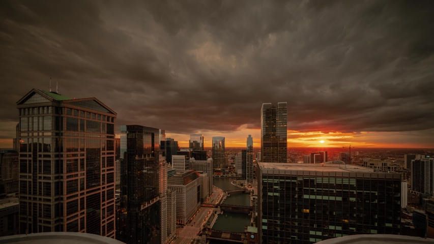 Panning down aerial time lapse of downtown Chicago with boats on river passing bridges along Wacker Drive as sun sets below the horizon lighting up clouds and lights come on in the city at night.