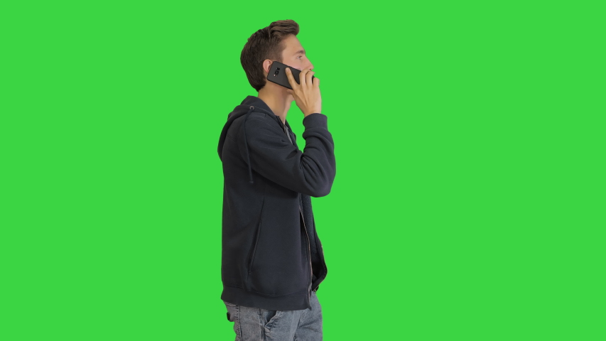 Casual man talking on mobile phone while walking on a Green Screen, Chroma Key.