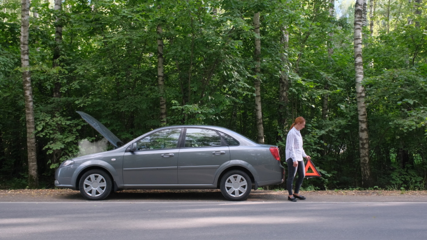 Woman installing red triangle sign in the forest. Misfortune on countryside road, female driver with broken automobile, car accident.