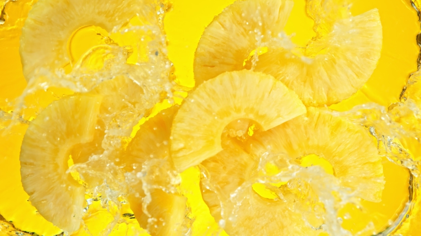 Super Slow Motion Shot of Pineapple Slices Falling into Water on Yellow Background at 1000fps.