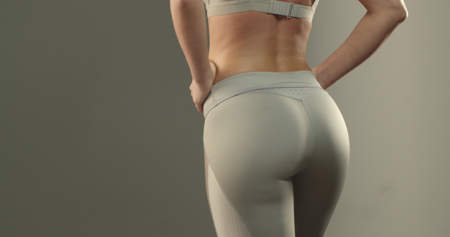 Close-up of sportswoman torso and lower body in sports leggings, woman workout, turning sideways to show booty and thigh exercises progress, show-off buttocks with strong gluteus Royalty-Free Stock Footage #1057493488