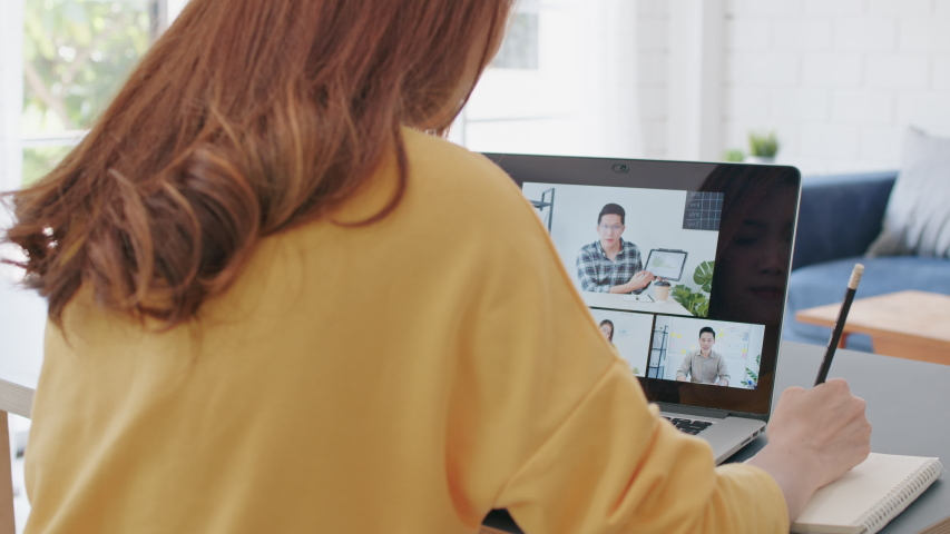Young Asian woman video call conference, online remote meeting with business coworker, at home. New normal lifestyle, social distancing, internet technology, businesswoman work from home concept Royalty-Free Stock Footage #1057494661