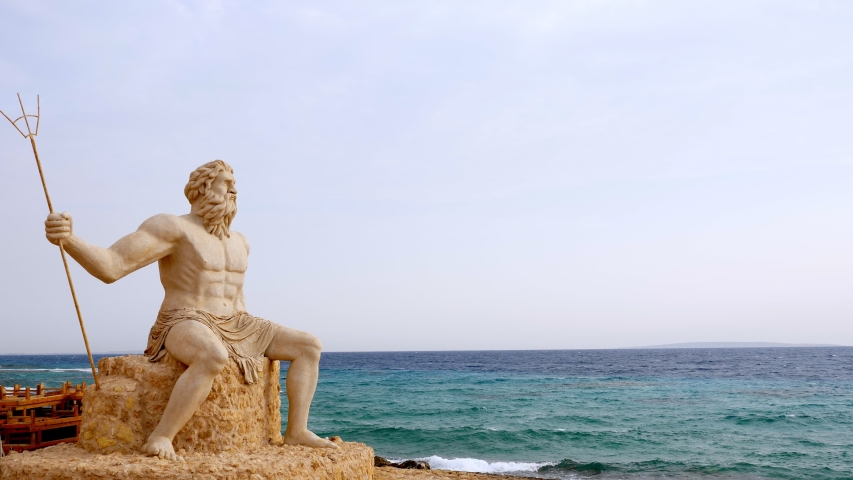 Monumental statue of God Poseidon on the beach, against the backdrop of the sea.