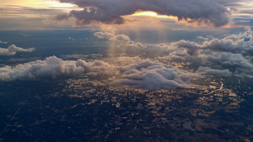 Amazing golden fluffy clouds moving softly on the sky and the sun shining through the clouds with beautiful rays. Sunset ,Sunrise with many white clouds many shapes, aerial view landscape of city. #1057512583