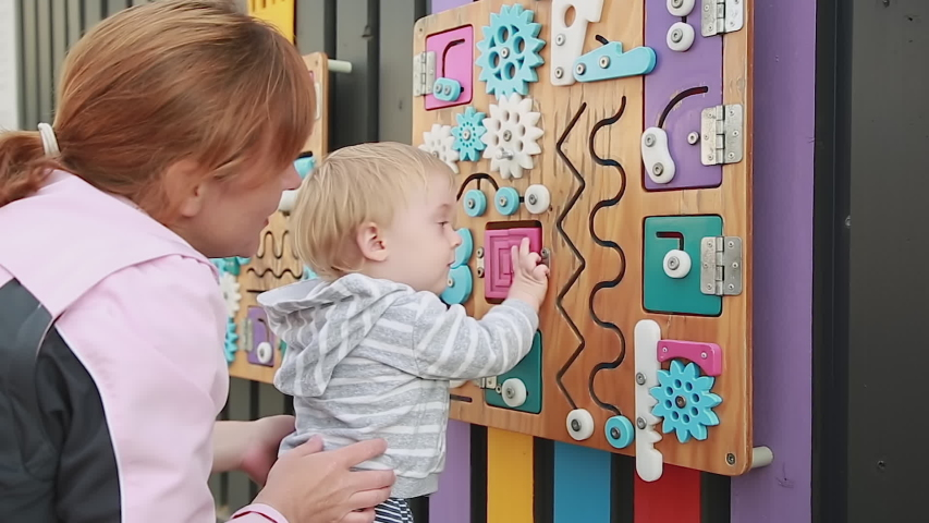 Mother And Child By Busy board. Cute baby boy playing with busy board on the wall. Educational toys. Busy-board for children. Wooden game board Royalty-Free Stock Footage #1057515514