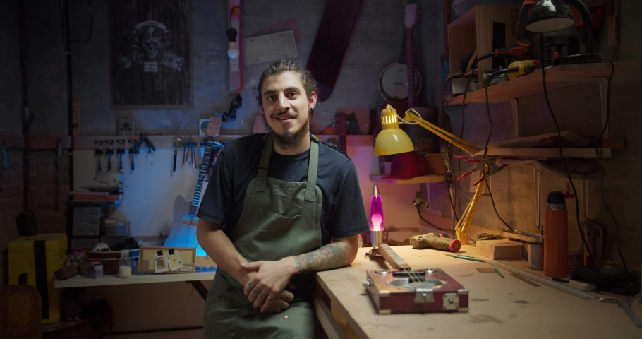 Slow motion portrait of professional foreman joiner standing dressed in apron in studio, confident specialist leaving on workbench table with tool instruments with colorful light on background   Shutterstock HD Video #1057516777
