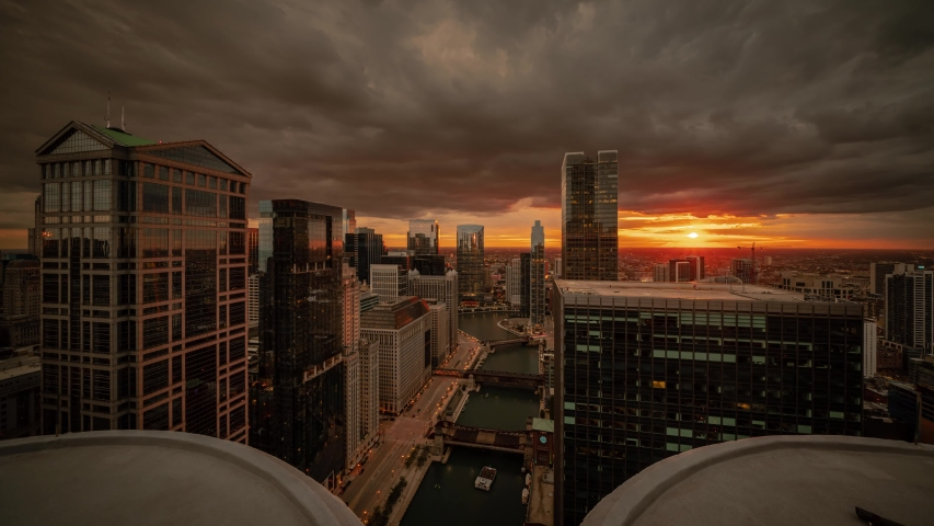Zoom in aerial time lapse of downtown Chicago with boats on river passing bridges along Wacker Drive as sun sets below the horizon lighting up clouds and lights come on in the city at night.