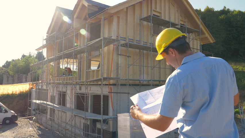 SLOW MOTION, CLOSE UP, LENS FLARE: Unrecognizable construction site manager looks at the floor plans while standing outside of a modern CLT house under construction in the countryside on a sunny day. Royalty-Free Stock Footage #1057523074