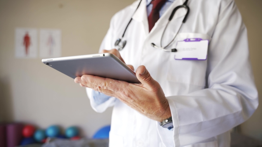 Caucasian doctor in surgeon coat on digital tablet capturing medical data Royalty-Free Stock Footage #1057525660