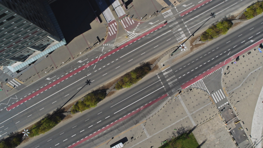 Top shot of Empty street in Warsaw city, Poland aerial view. Quarantined city, empty abandoned streets during corona virus outbreak. Drone shot flying over buildings, parked cars and street COVID