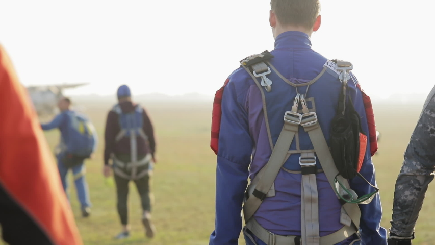 Back view of group professional skydivers going to the plane Royalty-Free Stock Footage #1057535086