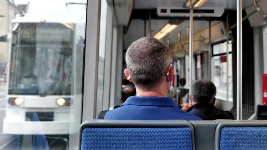Interior and selected focus view at the back of male passenger with face protection mask who sit in light rail tram or train in Germany during epidemic of COVID-19 virus with new normal concept. Royalty-Free Stock Footage #1057535758